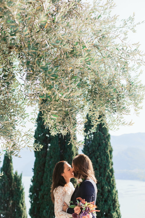 bride and groom kiss under tree only their heads are visible