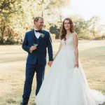 groom looks at his bride holding hands on grass outdoors