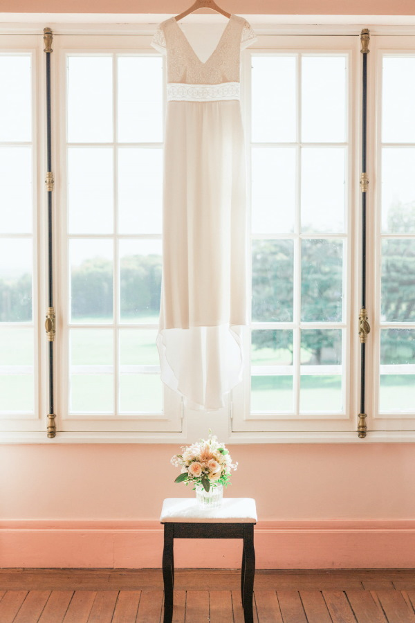 brides dress hangs in front of big windows with bouquet of flowers on a table underneath