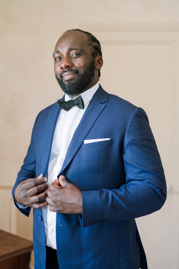 groom in blue suit black bow tie