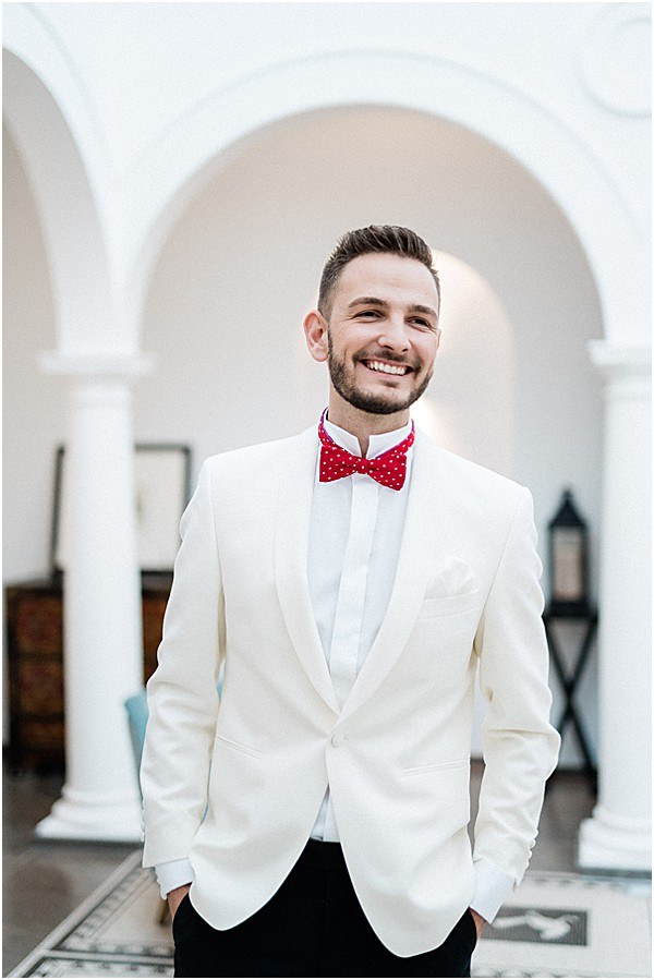 groom with red tie and white suit