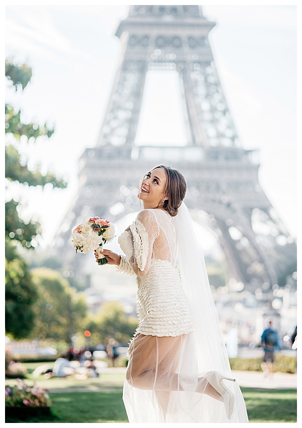 bride portrait in front of Eiffel tower kicking up beautiful heels