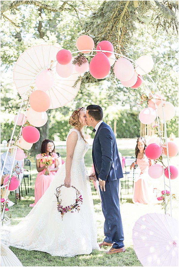 couple kissig under the balloon arch