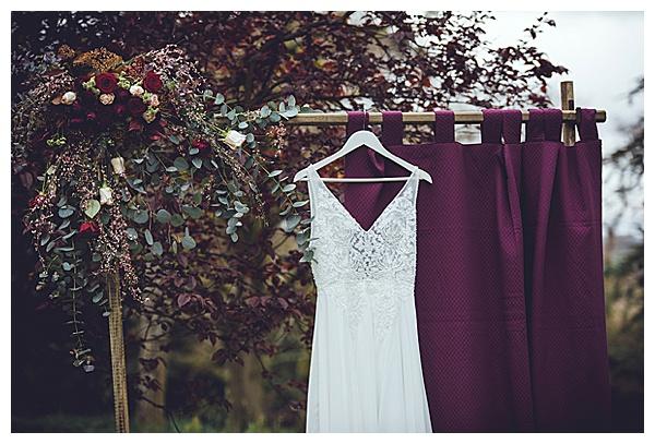 gown flower arch florist florals plum marsala color scheme