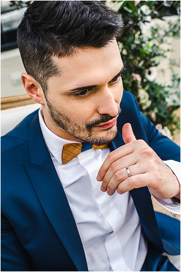 groom with wooden bow tie and navy suit
