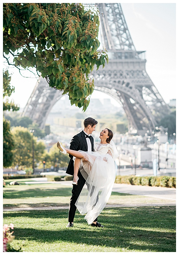 sweet couple dipping and twirling in front of the Eiffel Tower in Paris | Image by Helene Kos
