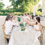Long bridal table of people making a toast at wedding outside Chateau de Courtomer