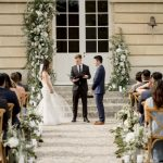 Wedding ceremony surrounded by white flowers and green foliage at Chateau de Courtomer