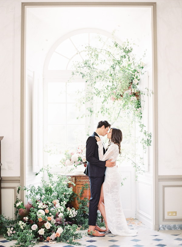 Bride and groom kiss in arched window surrounded by floral arrangements in the black and white tiled entrance hall of Chateau de Courtomer