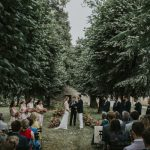 Moody shot of wedding ceremony amongst dark trees at Chateau de Courtomer