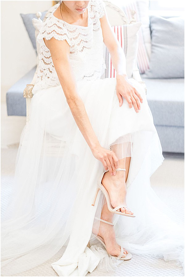 bride putting on her simple wedding shoes