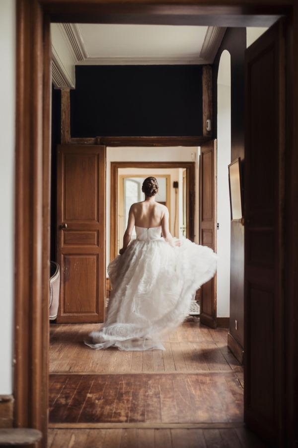 Bride walks through halls of Chateau Siradan in trailing dress