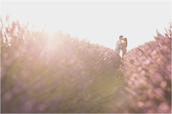 Engaged couple kiss in a lavender field