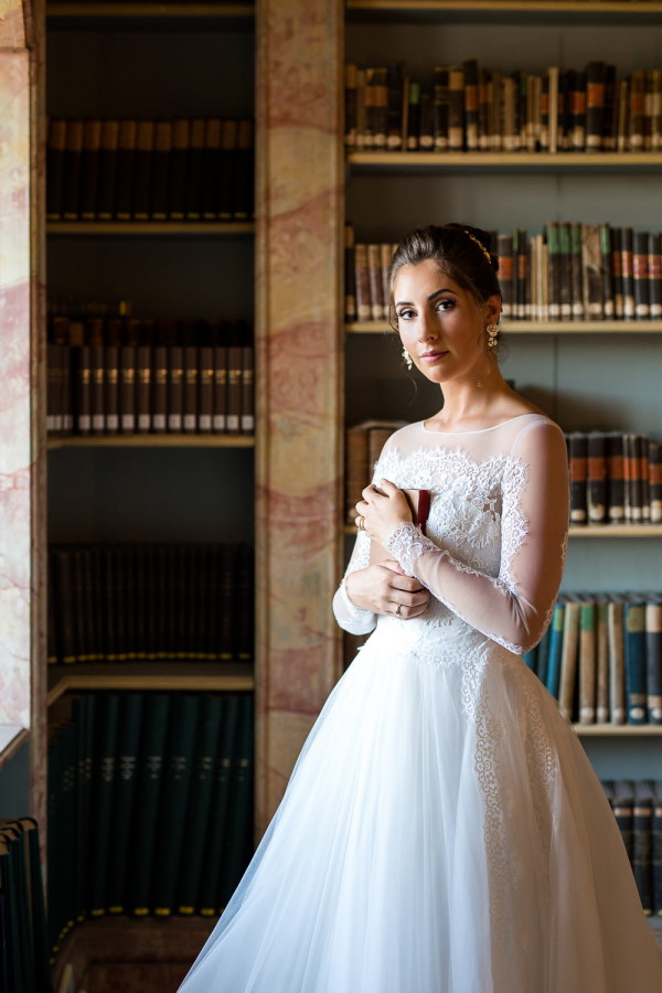 Bride holds book in Baroque library