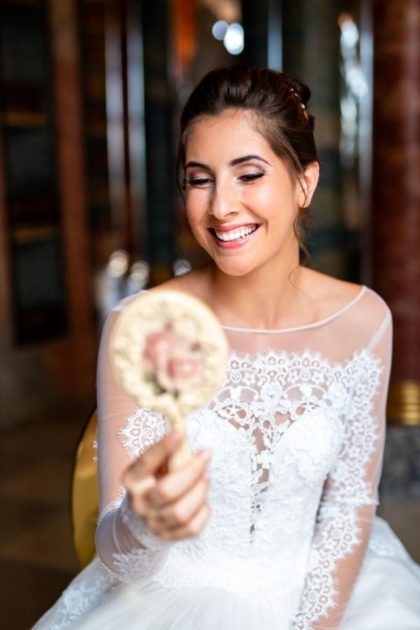 Bride looks in gilded hand mirror