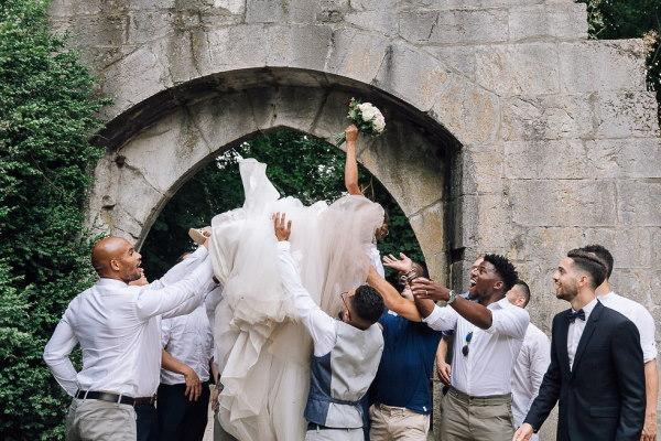 groomsmen throw bride into air