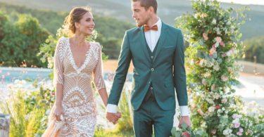 Newly-wed couple walk through gardens at pastel wedding