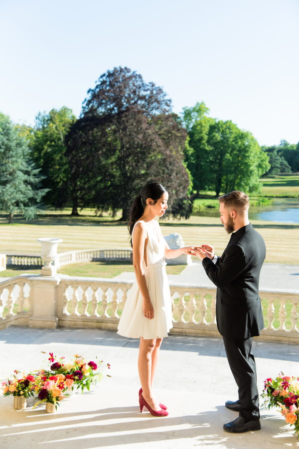 Groom puts ring on Brides finger in front of English Garden