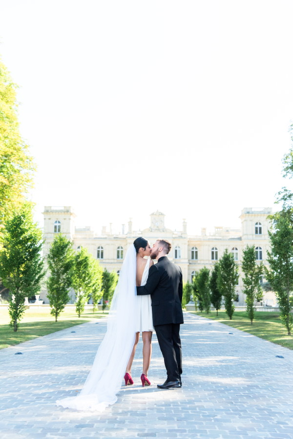 Couple Kiss with long veil of bride leading back to camera