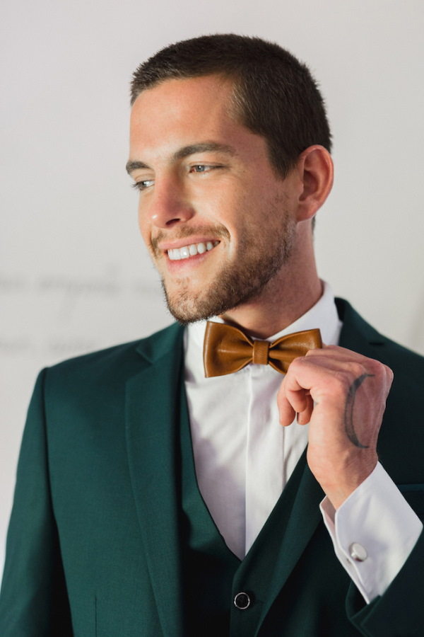 Groom in bottle green suit and brown leather bow tie