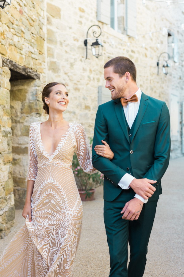 Bride and Groom arm in arm walk through French village