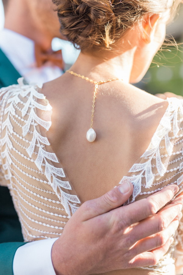 Back detail of brides dress and pearl necklace at nape of neck