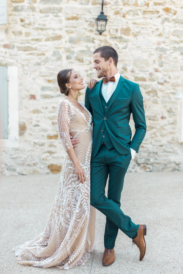 Bride in gown and groom in green suit pose lovingly