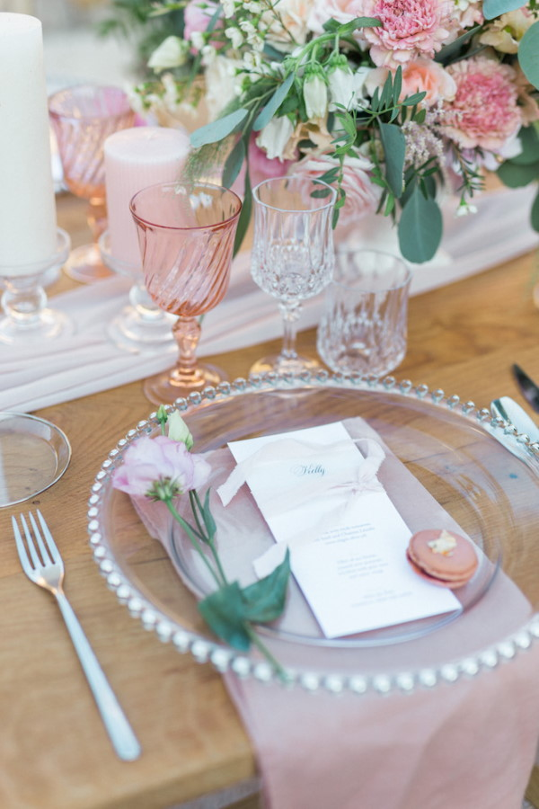 Pastel wedding table setting with pink champagne flutes