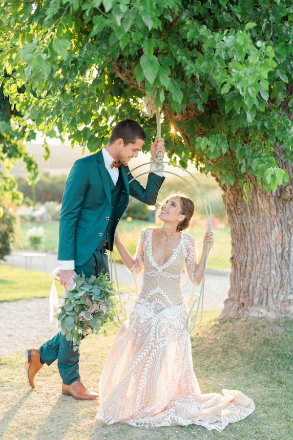 Bride on swing under tree looking at groom