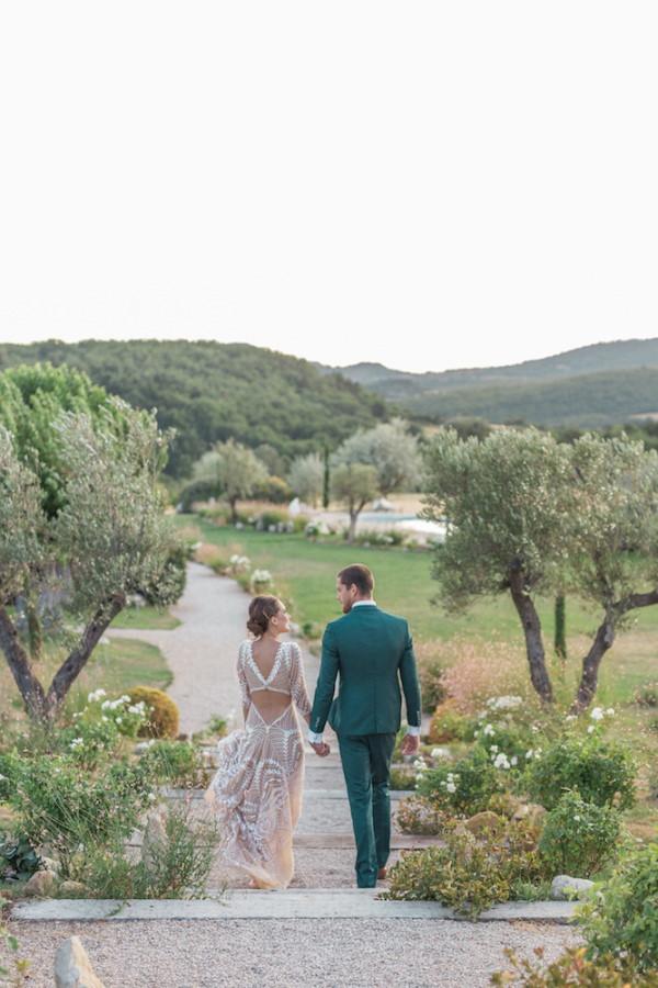 Bride and groom walk away through garden