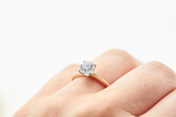 Rose gold and diamond engagement ring on woman's hand by Taylor & Hart