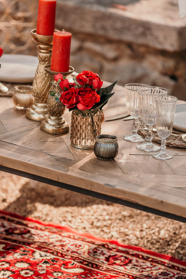 Red flowers and antique rug at asian themed wedding