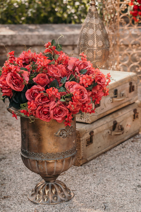 Red flowers fill antique brass vase next to vintage luggage