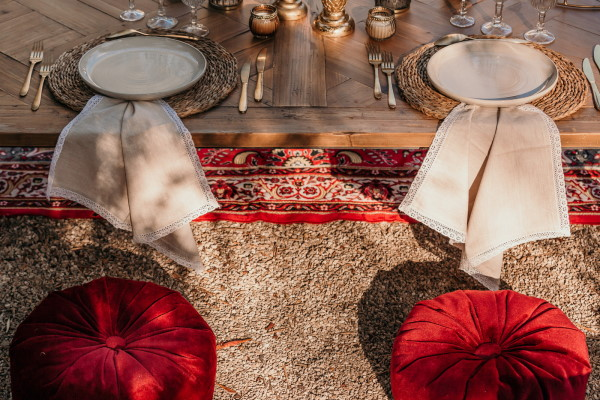Red cushion seating and antique rug for outdoor asian themed wedding