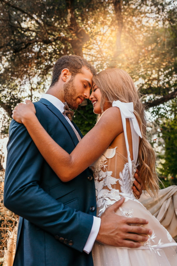 Bride and groom smile after kissing in afternoon sun