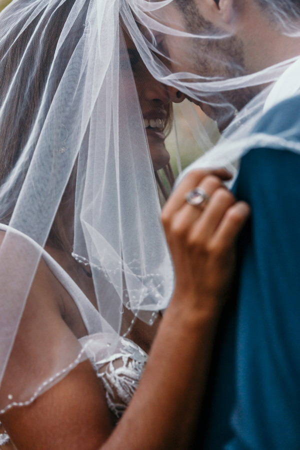 Close-up of bride in veil kissing groom