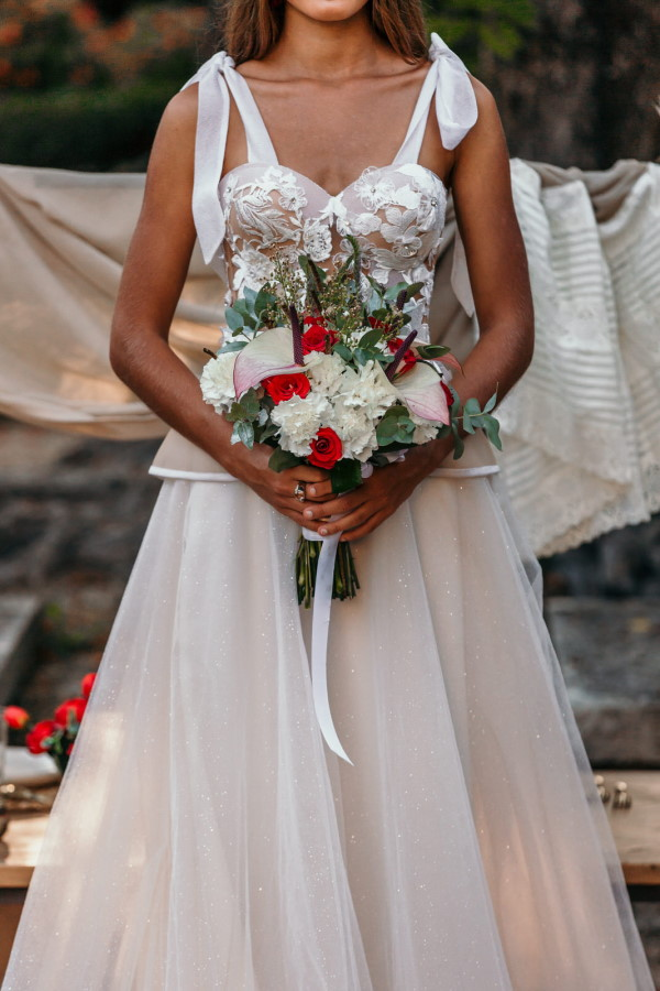 Closeup of bride holding red and white bouquet Bastide du Roy France