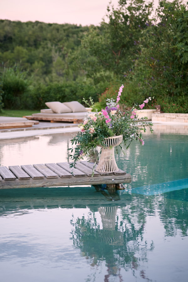 Pier with floral arrangement over infinity pool for wedding ceremony