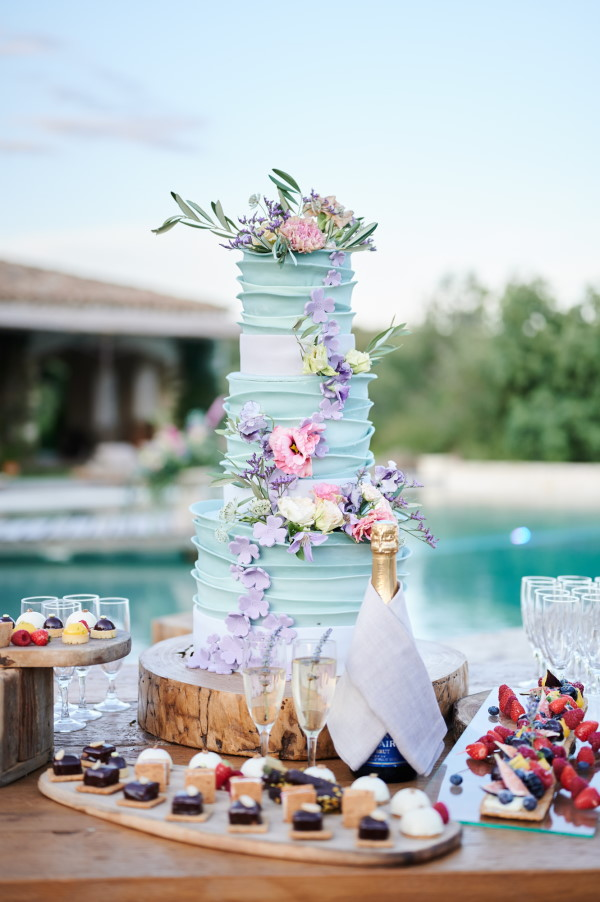 Beautiful 3 tier pastel blue wedding cake with rustic buttercream and fresh flowers
