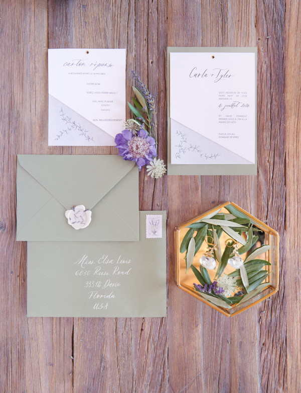 Wedding stationery in pastel green on rustic brown wooden table