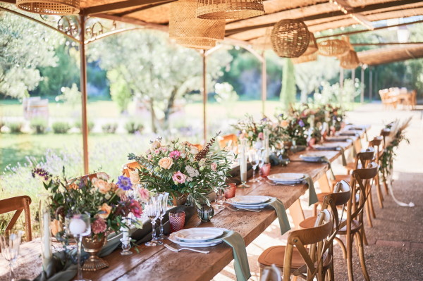 Rustic outdoor bridal table in converted stables with fresh flowers and raw wood table