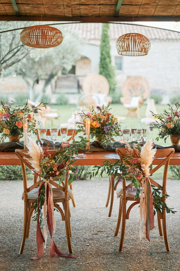 Floral arrangements tied with ribbon to the back of bridal chairs of rustic wood