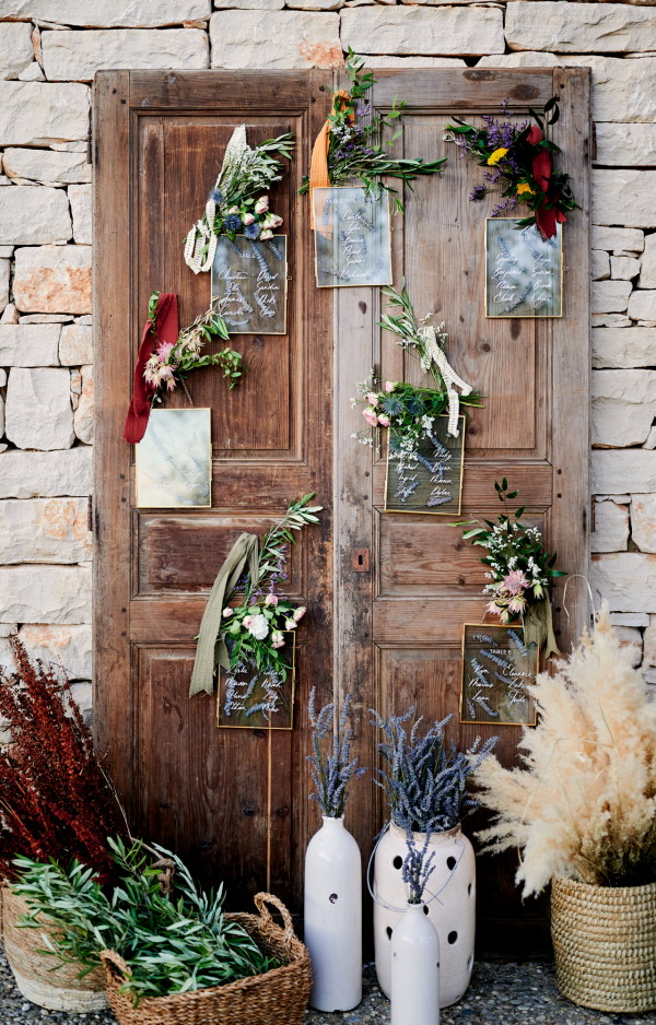 Porte-cochères doorway in raw wood with wedding seating plan and fresh flowers