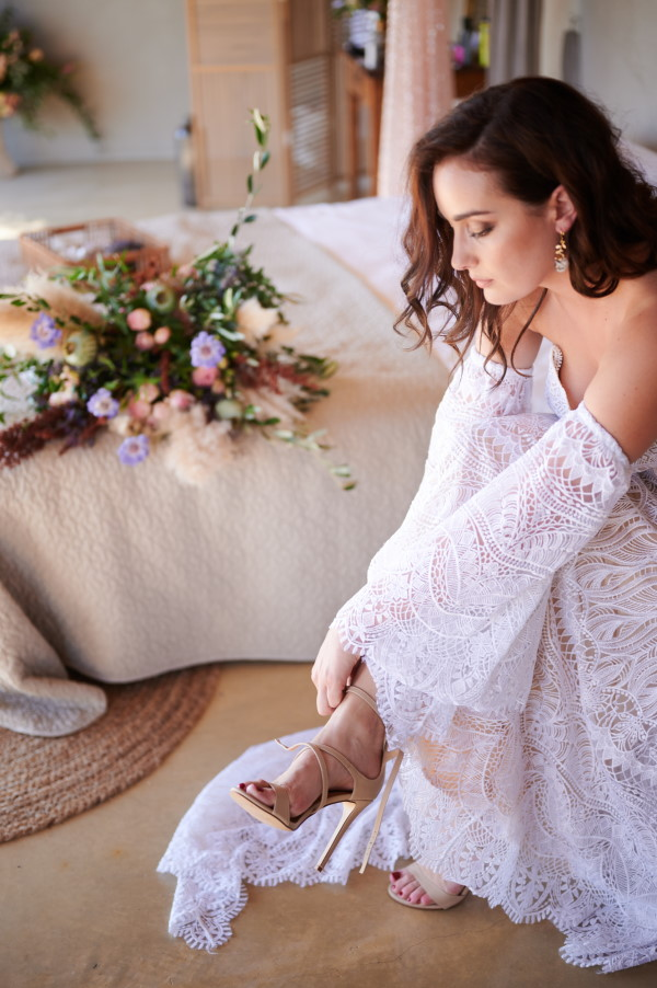 Bride puts on shoes in lace bohemian wedding dress