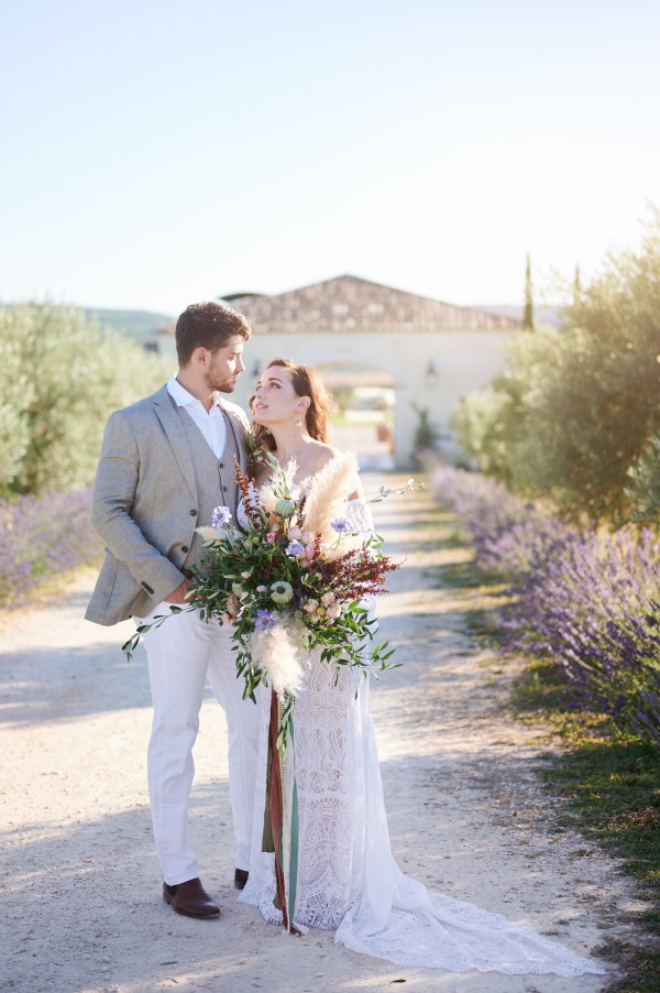 Bride and groom in bohemian style outfits with fresh bouquet in front of Domaine de Bres surrounded by Lavender