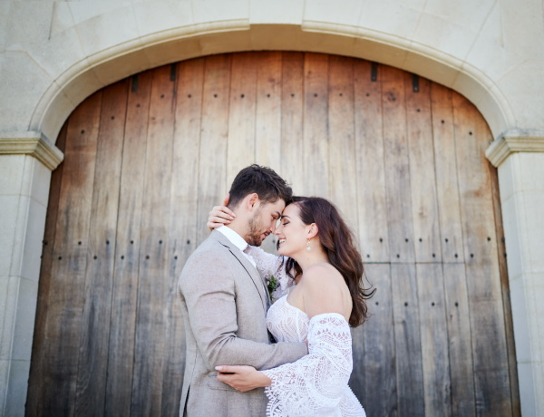 Bride and groom embrace in front of rustic wooden arch way