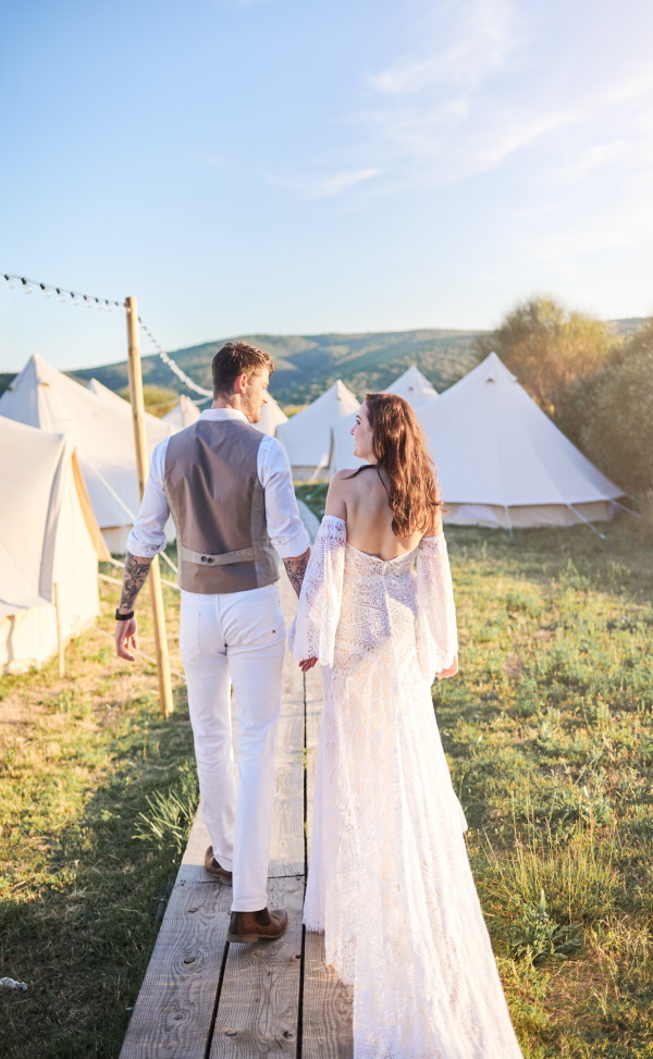 Bride and groom walk hand in hand in the afternoon sun by row of cotton tents for wedding guests