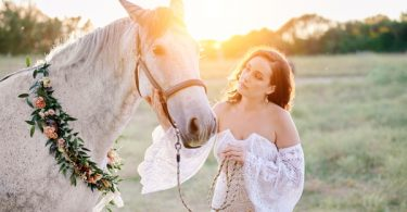Bride with grey horse wearing floral garland