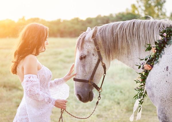 Bride pats horse with flower garland around it's neck