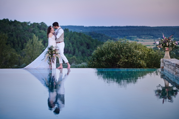 Bride and groom kiss at the edge of infinity pool